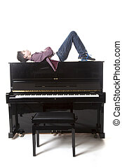 teenage boy lies upon upright piano in studio with white...