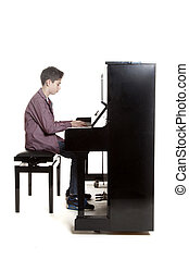 teenage boy sits at upright piano in studio - teenage boy...