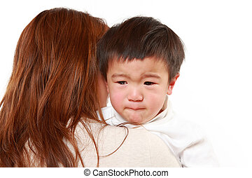 crying Japanese little boy who is being held by her mother