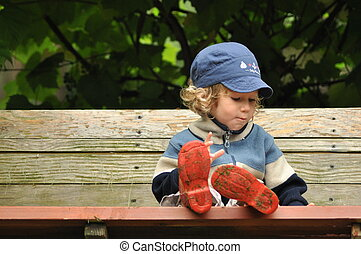 Boy in red rubber boots sitting on a rocking bench...