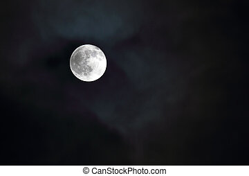 Full moon shining through clouds at night