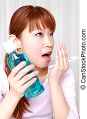 mouthwash - young Japanese woman breaths into her hand and...
