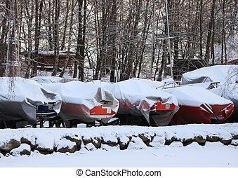 Sailing boats packed for the winter with snow