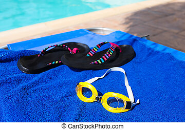 Swimming glasses and flip flops at the towel near swimming pool
