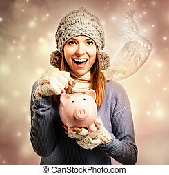 Happy young woman depositing money into her piggy bank -...