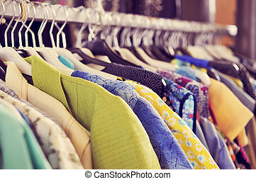 clothes hanging on a rack in a flea market - some used...