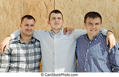 Three male friends standing arm in arm in front of a wooden...