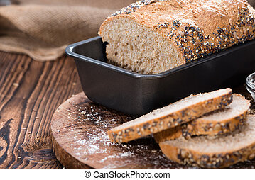 Homemade loaf of bread on dark wooden background