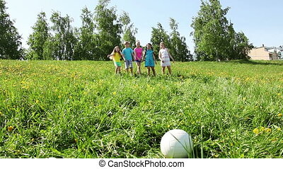 Kids running to the ball in field