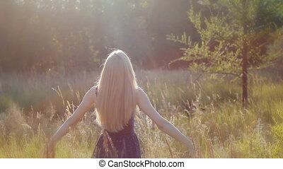 The blonde girl rase her hand to the sun. Freedom concept. -...