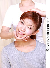 chiropractic - portrait of young Japanese woman getting...