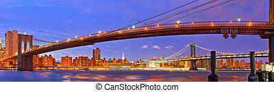 New York City, USA. Brooklyn and Manhattan bridges at sunset with colorful lights