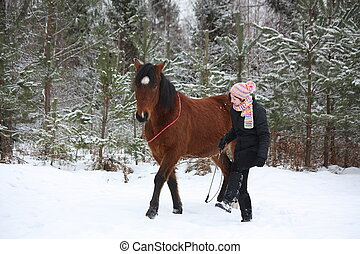 Teenager girl and brown horse walking through the forest...