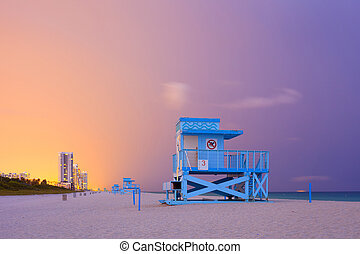 Summer scene in Miami Beach Florida, with a blue lifeguard house in a typical Art Deco architecture, at sunset with ocean and colorful sky in the background