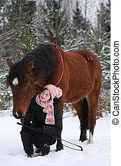 Beautiful teenager girl sitting near brown horse in winter -...