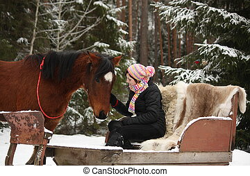 Teenager girl sitting in the sled with furs and brown horse...