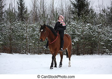 Teenager girl riding horse without saddle and bridle in...