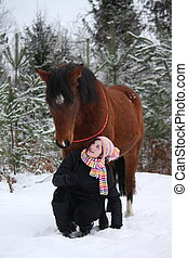 Beautiful teenager girl sitting near brown horse in winter -...