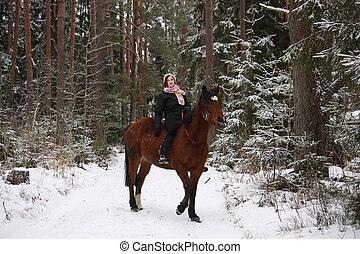 Beautiful teenager girl riding brown horse in the forest -...