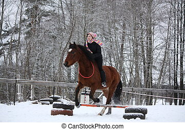 Teenager girl with brown horse show jumping without bridle...