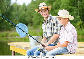 Summer angling - Father and son sitting on bridge and...