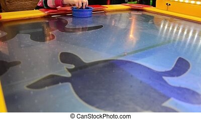 Little girl with mother playing air hockey