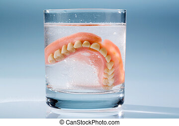 denture in water glass - a denture is cleaned in a glass...