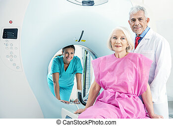 Woman in 60s ready to undergo MRi scan, assisted by two...