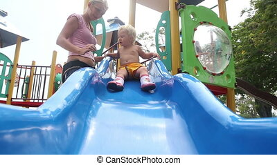 daughter and mother play on playground - Mom rolls her...