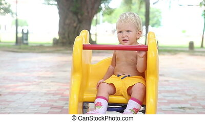 baby sitting on a yellow rocking