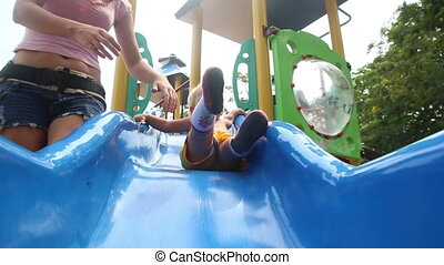 daughter and mother play on playground