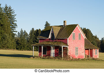 Dilapidated vacant red house in a nice grass field under...
