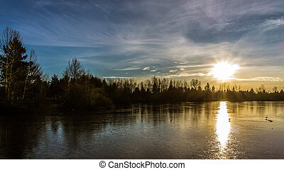 Sunset over frozen lake - Sunset over frozen Mill Lake in...