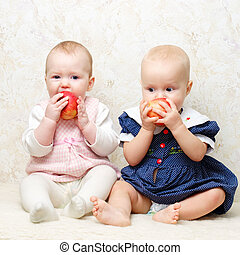 Two infants with apples - Two little baby girls eating...