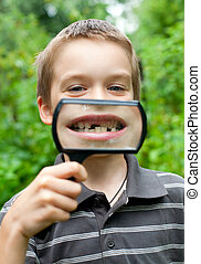 Deciduous teeth - Young boy showing missing baby tooth...