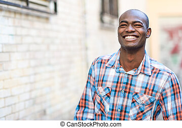 Black man wearing casual clothes in urban background -...