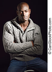 Black man wearing casual clothes in black background -...
