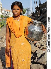 Water in Poverty - A poor Indian teenage girl carrying a pot...