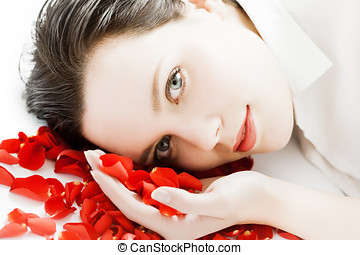 Woman With Petals - Young woman laying on floor with rose...