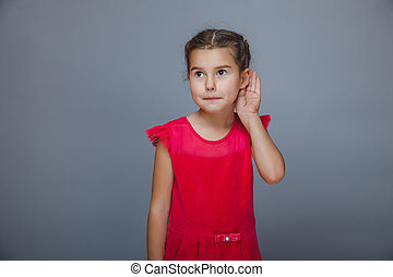 girl holds the hand of a child listening to ear on gray back...
