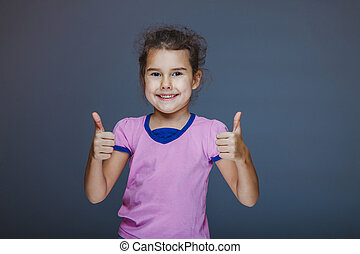 Girl showing thumbs up sign yes on a gray background - Girl...