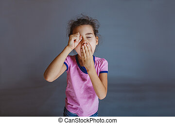 girl yawns t hand over his eyes on gray background - girl...