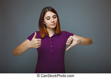 Girl showing sign of yes and the no on a gray background -...