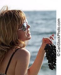 Woman with grape on beach - Woman in bikini holding grape on...