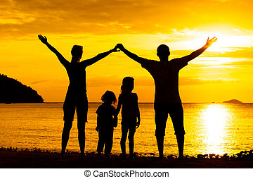 Silhouette of happy family who playing on the beach at the...