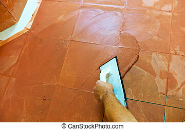 grout is applied - a tiler carries on floor tiles on the...