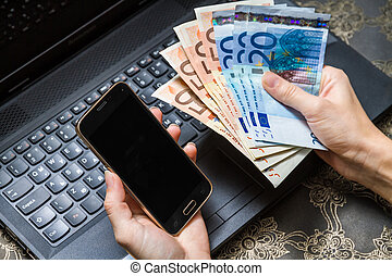 Smart phone and computer for on line payment - Woman is...