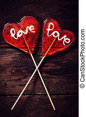 Heart couple - Couple of heart shape lolly pops on wooden...