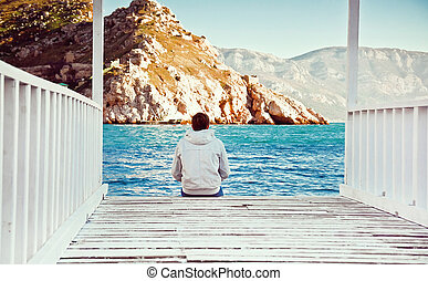 lonely young man sitting on the dock