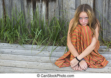 Young hippie girl sitting on the ground outdoors Picture...